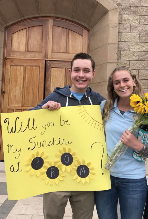 Jacob+Gunderson+%E2%80%9819+asks+Hailey+Colman+%E2%80%9819+to+prom+after+morning+Mass+on+Tuesday+with+sunflowers+and+a+poster.+The+annual+school+prom%2C+a+formal+dance+for+CCHS+upperclassmen%2C+will+be+held+at+SeaWorld+on+May+11.+