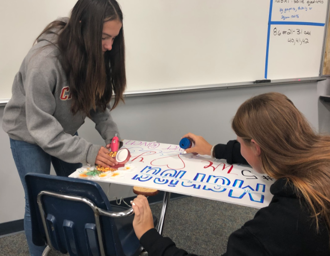 Varsity softball players Jenna Mello '21 (left) and Sophia Manos '21 collaborate to create posters for Senior Night, the team's last league game Tuesday against Patrick Henry High School when it will honor the team's four seniors.