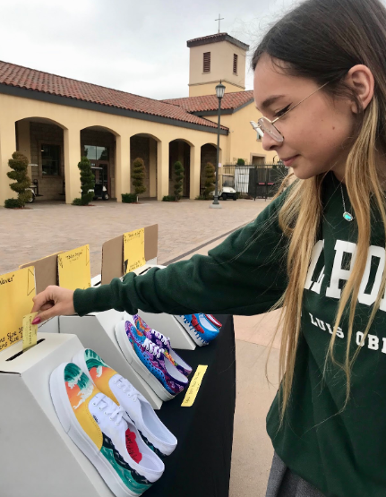 """In support of CCHS National Art Honors Society fundraiser, Gabrielle Charest '19 places her $5 raffle ticket with the vibrant shoe composition titled """"Waves. The proceeds of this fundraiser will be donated to Fr. Joe's Villages, a program that serves the homeless population in San Diego by providing them with food, shelter, and medical care."""