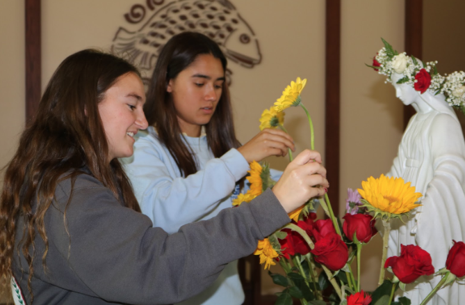 """Marie Temprendola '19 (left) and Veronica Edwards '19 (right) adorn a statue of Mary with yellow daisies while the club sings """"Hail Holy Queen"""" during the May Crowning ceremony held by the Rosary Club at lunch on Tuesday. The club proceeded to pray the glorious mysteries of the rosary in honor of May being Mary's month, a practice that has been in the Catholic Church since the 13th Century."""