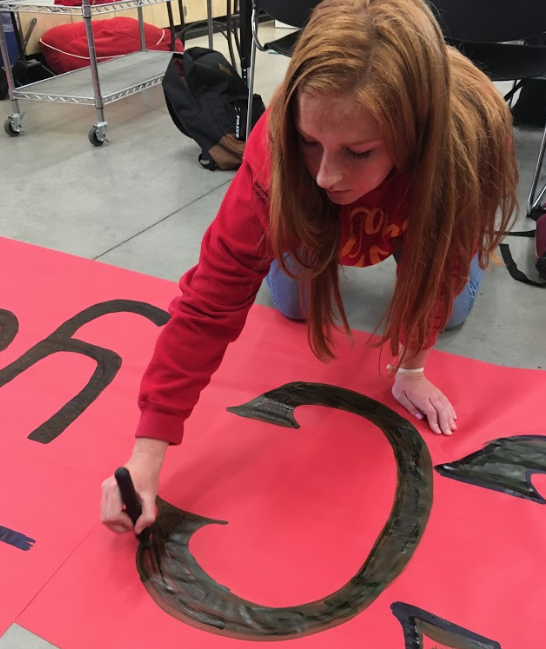Molly Curran '22 paints the Associated Student Body sign, which hung in front of the student section during Friday's football game against La Costa Canyon High School.