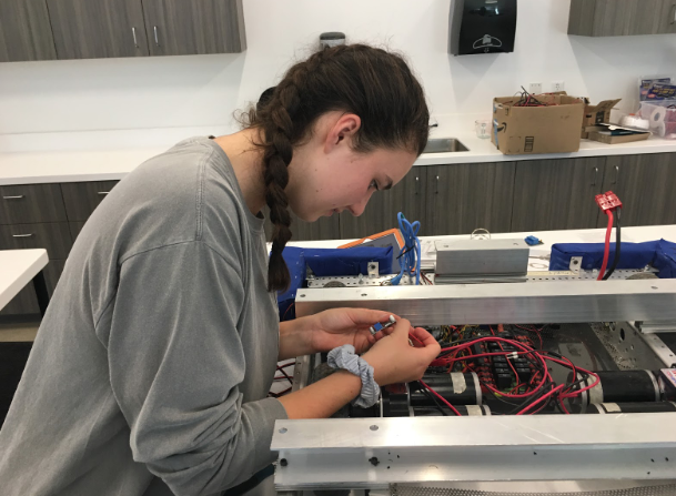 Christine Walsh '20, a member of the Cathedral Catholic High School robotics team, Pacific Steel, connects the power distribution panel to the step-down module in a robot which will be featured in the upcoming fall rally.