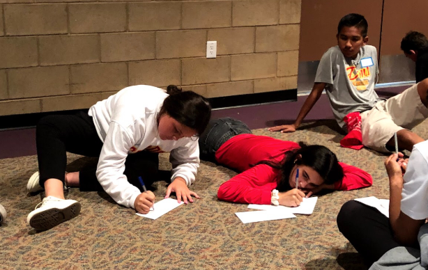 Jacqueline Mossy '23 (left) and Bella Moreno '23 (right) write letters to their senior selves during freshman retreat Thursday. The letters will be sent to the freshmen at the end of their senior year. Retreat consisted of Mass, games on the football field, a speaker, and the letter-writing.