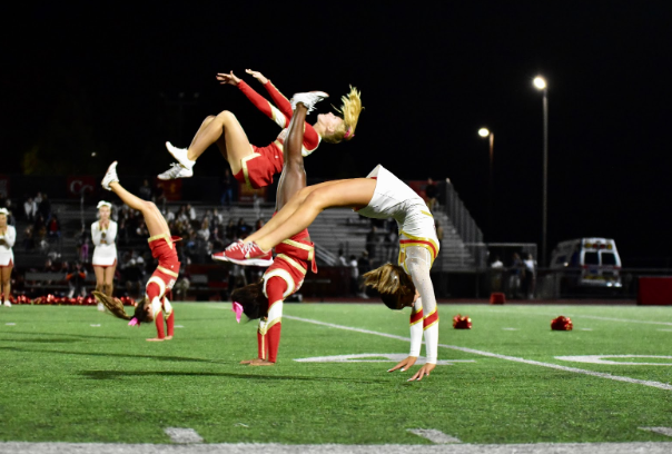 Cathedral Catholic High School Varsity Cheerleaders do backhand springs in front of the home audience on the field during halftime of the homecoming game.