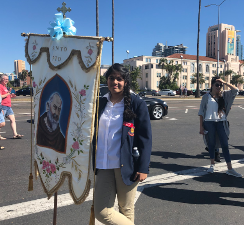 Treasa Paul '21 carries a banner during the Our Lady of the Rosary Festa in Little Italy Sunday. Paul, among other CCHS ambassadors, carried banners during the procession from the church to Embarcadero, where the priests blessed a fishing boat and the crowd enjoyed fireworks. The CCHS band marched in the procession, playing music and leading the way.