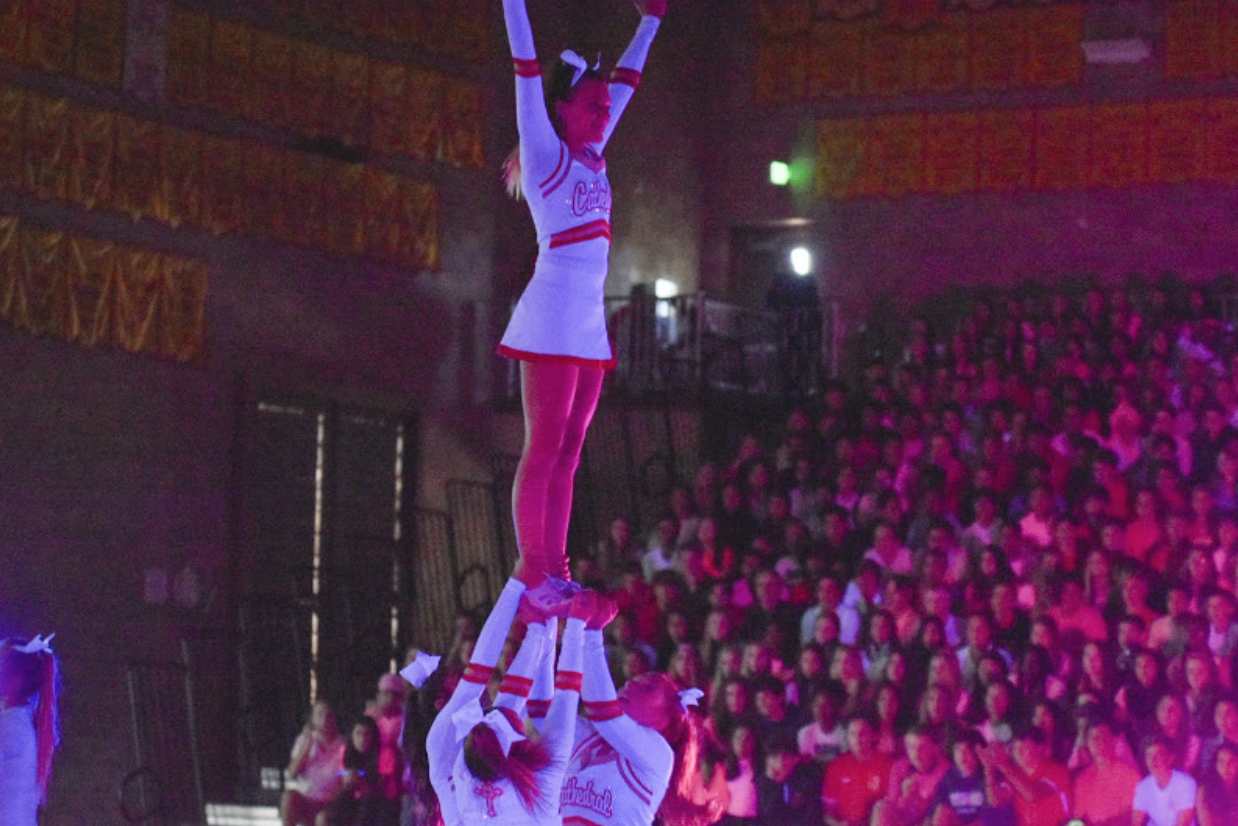 Kelley Hallinan (top) performs a routine with the rest of the cheer squad along with the rest of the cheer team, showcasing their talent through various stunts and dances.