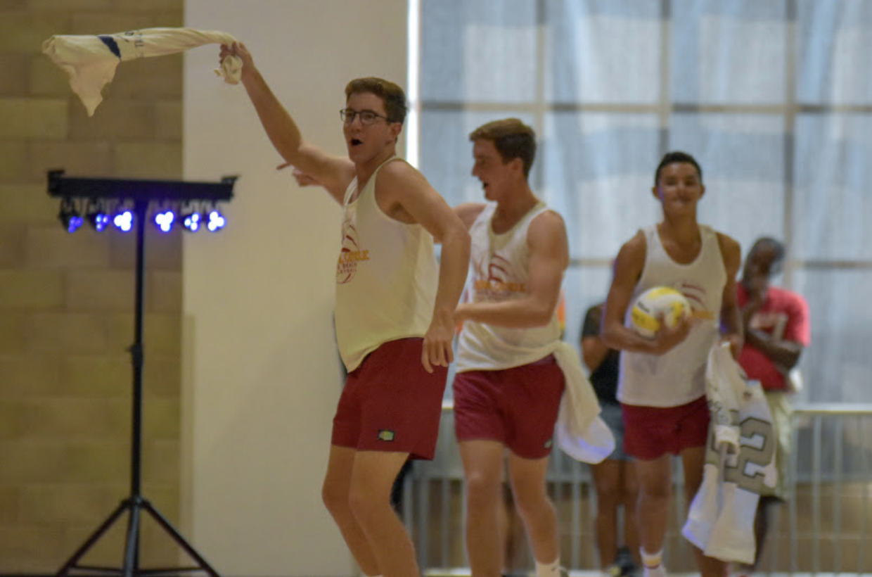 Cameron Nash '20, Nate Nash '20, and Jackson Reed '20 [Left to right] run out during the short showcase for the boys sand volleyball team showcase during the rally with their t-shirt turned rally towels in hand.