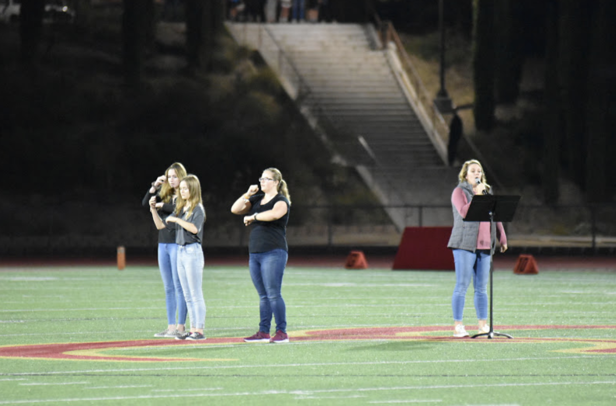 CCHS alumna Mrs. Kayla Tucker '10 sings the American National Anthem before the football game while American Sign Language Honor society members Michelle Welsh '20, Kate Foster '20, and Emma McIntosh '21 sign the national anthem.