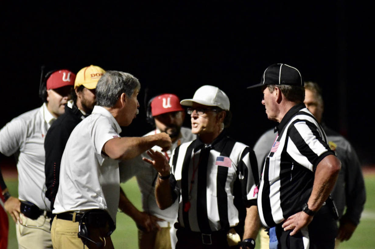 Varsity football head coach Mr. Sean Doyle passionately discusses a previous call made by the game officials during the second quarter in hopes of convincing them to reverse the call.
