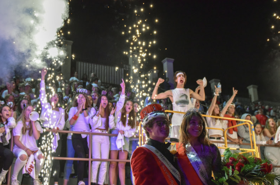 Homecoming king and queen Adam LeClair '20 and Olivia Schleicher '20 (bottom right, left to right) pose for a photo in front of the Los Locos moments after the football team team won the homecoming game last October.