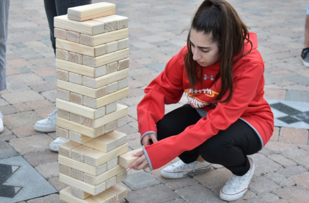 "Alyssa Shamoon '20 engages in a game of Jenga during Thursday's Campus Ministry/XLT night, themed ""Get Pump(kin)ed for Jesus, which featured games like can jam and ping pong, pizza and apple cider, and a photo booth to match the theme. The students spent the following hour in the chapel for adoration and confession by Father Richard Castro and Father Paul de Soza, with music by Pat Villa."