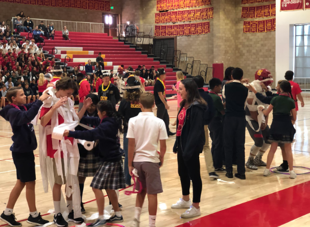 Eighth grade students use toilet paper to compete wrapping seniors as mummies during Dons Day, a yearly event to share the Cathedral Catholic High School community to local junior high school students.