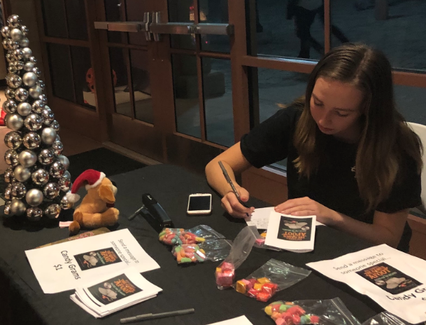 Jenna Crowley '23 writes a candy gram to a crew member of the CCHS fall production of The Game's Afoot at the Friday night production.