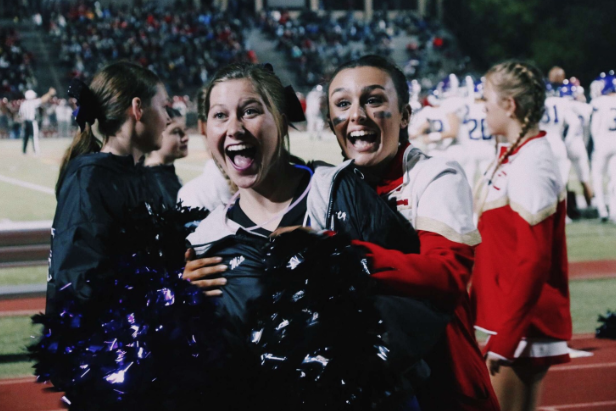 Cathedral Catholic cheerleader Sam Smith '20 (right) embraces Carlsbad High School cheerleader, Mia Penrod '20 (left), as the bittersweet moment of the football season came to a close at Manchester Stadium on last November.
