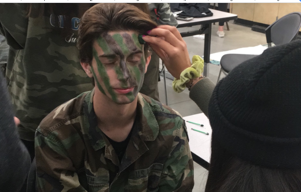 Faith Miller '20 applies face paint to Alex Carrieri '20 before the first Cathedral Catholic High School football playoff game against Carlsbad High School at home, where the team lost 21-20 after a missed 2-point conversion.