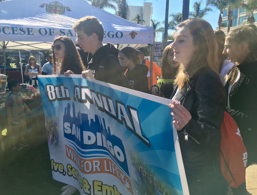 Cecilia Bacich '20, Anthony Graf '22, and Emily Rotunda '20 (left to right) hold the banner to lead the 8th Annual San Diego Walk for Life, which approximately 4,500 people attended, in order to advocate for the rights of the unborn.