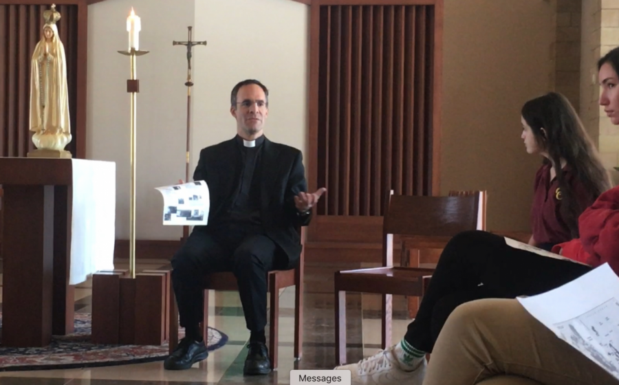 Father Paul de Soza leads a prayer before the map during break Thursday during Life Week with approximately 20 CCHS students. The prayer consisted of a moment of silence to offer intentions for those people around the world affected by disaster and poverty.