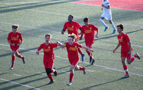 The CCHS junior varsity boys soccer team rejoices after Connor Douglas '22 scores the winning goal against Saint Augustine High School at CCHS in February.