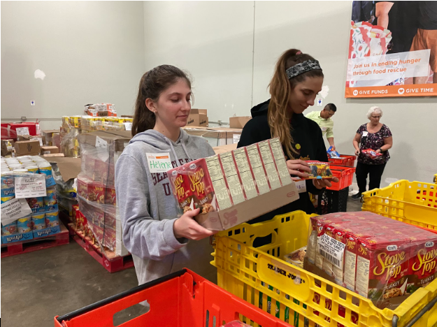 Helene Boggs '20 and Julia Van Wey '20 (left to right) organize dry food items at the Feeding San Diego food distribution warehouse. Approximately 10 Cathedral Catholic High campus ministry students attended Tuesday to help organize food to help feed impoverished San Diego residents.